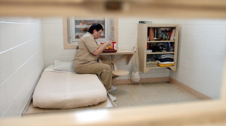 Kelly Gissendaner (cq), the only woman on Georgia's death row, eats lunch in her 9-by-12 cell at Metro State Prison in Atlanta, Tuesday, July 6, 2004. The shelving unit at right holds all her possessions. She's photographed through the slot in her cell door through which guards pass Gissendaner her lunch tray and other items throughout the day.  (AP Photo/Atlanta Journal-Constitution, Bita Honarvar)