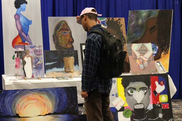 Hampton students look at the art on display at the Hip Hop conference. (Joanna Rowell//Hampton Script)