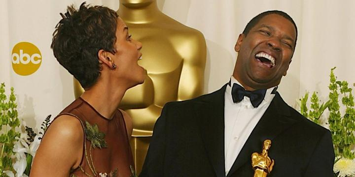 """HOLLYWOOD, : US actor Denzel Washington (R) and US actress Halle Berry (L) share a laugh while holding their Oscar statues after winning the award for best actor in a leading role (for """"Training Day"""") and best actress in a leading role (for """"Monster's Ball"""") 24 March, 2002 at the 74th Academy Awards at the Kodak Theater in Hollywood, CA. Washington is the first African-American actor to take home the statuette in the top actors category since 1963 when Sidney Poitier won for """"Lilies of the Field"""" and Berry is the first African-American actress to ever win the top award in a leading role. AFP PHOTO/Mike NELSON (Photo credit should read MIKE NELSON/AFP/Getty Images)"""