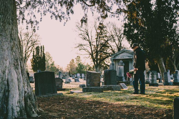 man-in-black-jacket-standing-in-front-of-grave-3648309